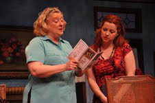 Margaret (Gayle Grimes) examining a religious pamphlet given to her by the Evangelical Melissa (Lori Brooks). Phot courtesy of Reston Community Players.