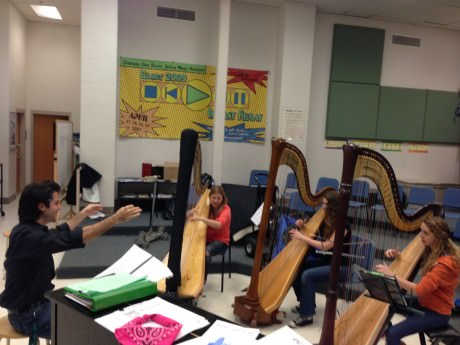 Kristofer Sanz rehearsing with harpists Monika Vasey, Vivian Franks, and Nora Kelsall.