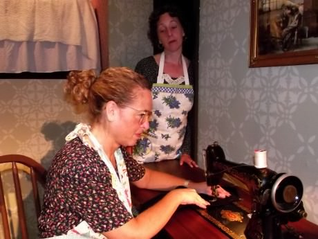 Jill Goodrich (Blanche) at Sewing Machine and Nora Zanger  (Kate). Photo by Roy Peterson.