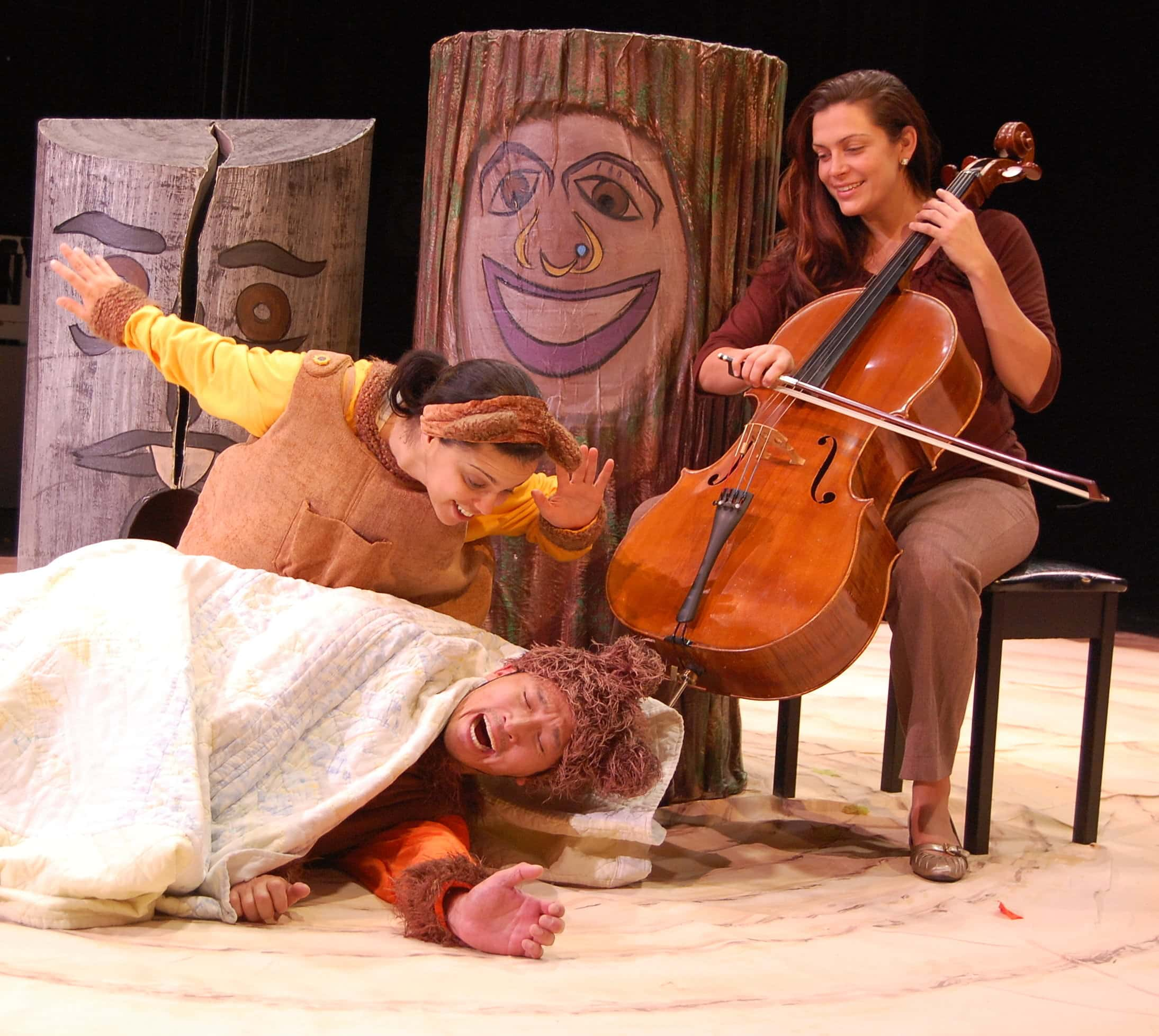 As Winter winds down, Sister Bear wakes up Brother Bear from hibernation. Accompanying  their journey through the seasons is live cellist, Katie Chambers. (L to R Nora Achrati, Jacob Yeh, and Katie  Chambers). Photo by Laura DiCurcio.
