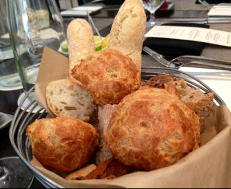 A basket of gougeres and assorted in house baked breads.