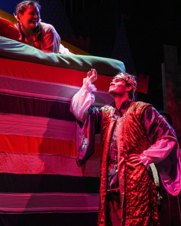 Prince Dauntless (Mike Culhane) holds the tiny pea that was buried under all the mattresses of Princess Winnifred's (Meg Nemeth) bed. Photo by Andrew Culhane.