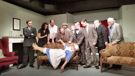 The cast gathers around Mrs. Rogers who fainted after the accusation. From left to right - Anthony Marston (William Stiles), Vera Claythorne (Emma Jensen), William Henry Blore (Chris Carothers), Dr. Armstrong (Dave Chalmers), Fred Narracott (Rocky Nunzio), Miss Emily Brent (Phyllis Kay), Sir Lawrence Wargrave (Larry Simmons), Captain Lombard (Kyle Kelley), Rogers (Jim Berard), General Mackenzie (Ron Able), and Mrs. Rogers (Ilene Chalmers) on the couch. Photo by Richard Atha-Nicholls.