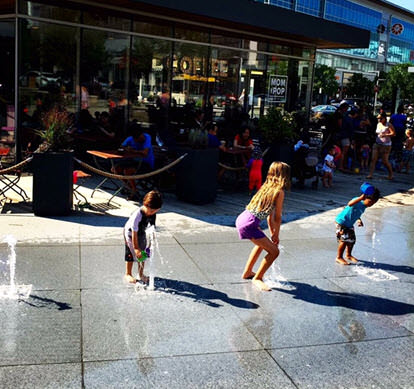 Kids frolic in the fountains outside Mom & Pop's – photo credit Julie Jakopic.