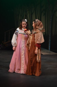 Snow White (Zoe Rocchio) is greeted with an apple from the Crone (Gabrielle Schaubach). Photo by Larry McClemons.