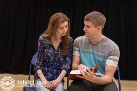 Adam (Scott Duvall), a young writer, uses a Bible to teach android performer Jacie (Caity Brown), how to read. Photo by Irish Eyes Photography by Toby.