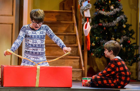 Ralphie (Ben Pedersen) opens his Christmas gift while little brother Randy (Aidan Crane) watches. Photo courtesy of Media Theatre.