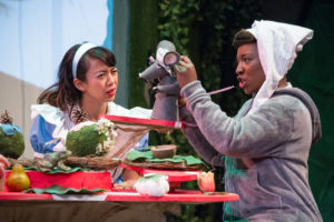 The Dormouse (Mabelle Fomundam) tells a story to Alice (Alexandra Palting). Photo by C. Stanley Photography