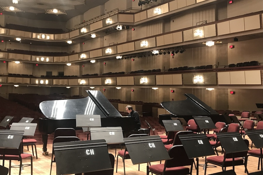"""Pianist Pierre-Laurent Aimard tests out the acoustics in the hall before the concert. Could he be playing the program piece Piano Concerto No. 5 in E-flat major, Op. 73 (""""Emperor"""") by Beethoven, or Chopsticks? The world may never know! Photo by Samantha Pollack."""