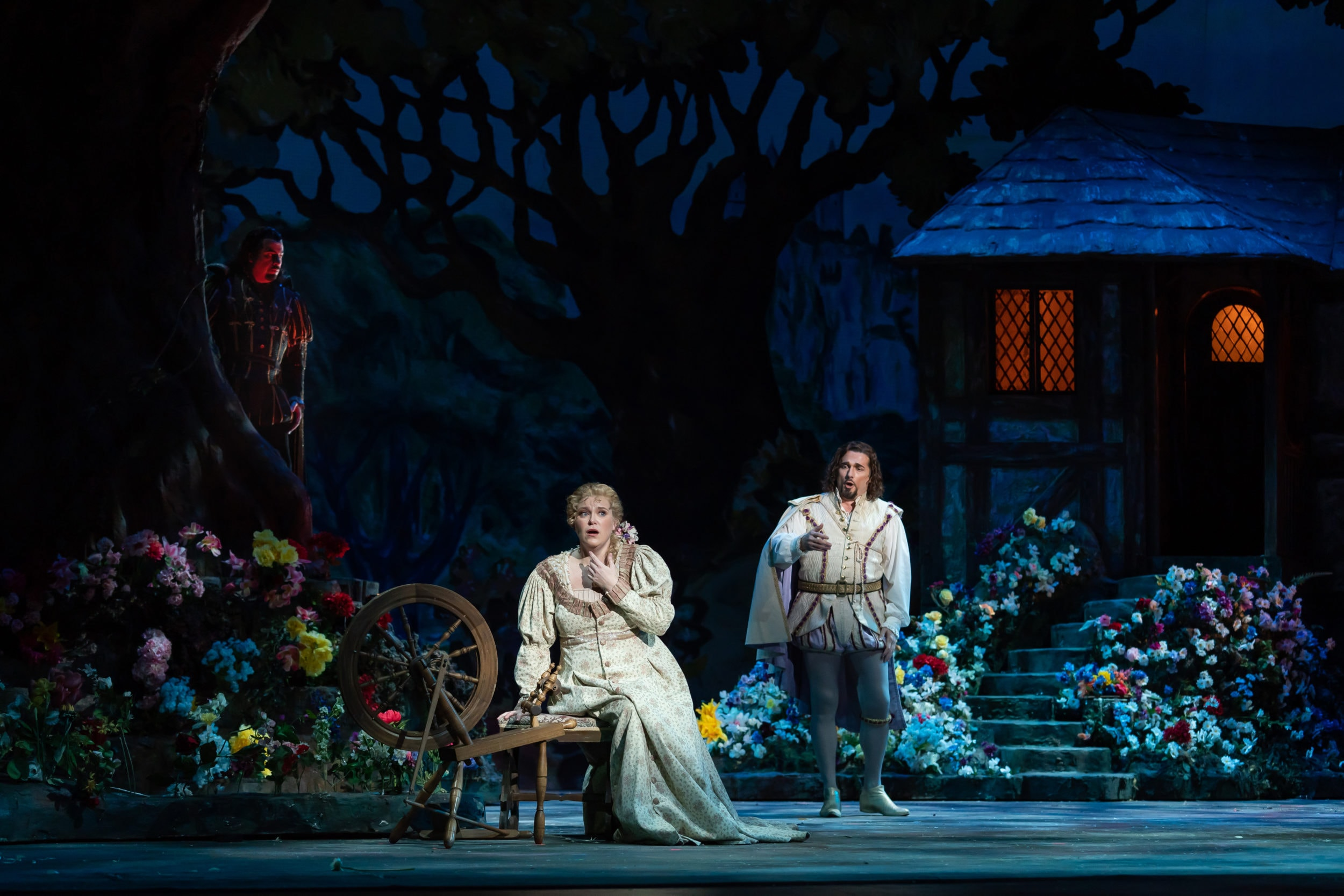 The devil (Raymond Aceto) looks on as Faust (Marcelo Puente) woos Marguerite (Erin Wall) in WNO's production of 'Faust.' Photo by Scott Suchman.