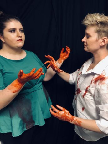 Lady Macbeth (Leandra Lynn) and Macbeth (Sarah Pfanz) with blood on their hands. Photo courtesy of Britches and Hose Theatre Company.
