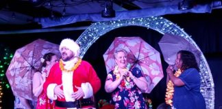 """Joey Olson, backed by Katie Pond, Kat Brais, and Lisa Alford, sings """"Traveling Man"""" in StageCoach Theatre Company's 'Santa's Funky Hawaiian Christmas Cabaret.' Photo by Laura Mills."""
