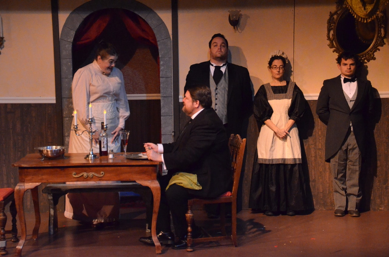 Viscount St. Galen (Jim Adams) compliments Myrna Fielding (Pamela Northrup) on her first meal cooked at his manor as Mr. Henderson (Michael Iacone), a maid (Jeannette Connors) and a footman (Tyler Dos Santos) stand by. Photo by Kris Northrup.